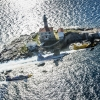 Nigel Lamb of Great Britain, Hannes Arch of Austria and Peter Besenyei of Hungary fly in formation in front of the lighthouse tower of Rovinj prior to the second stage of the Red Bull Air Race World Championship in Rovinj, Croatia on April 10, 2014.