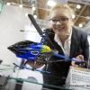 Eine Mitarbeiterin der Firma Jamara Germany e.K. stellt einen Helikopter vom Model e-rix 250 mit Blatthaltern aus eloxiertem Aluminium in eine Vitrine (An employee of the company Jamara Germany e.K. places a helicopter from Model e-rix 250 with blade holders made from anodised aluminum in a showcase)